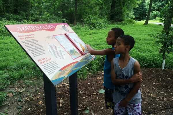 Two young boys read an informative trail marker along the Schuylkill River Trail within the Schuylkill River Heritage Area.