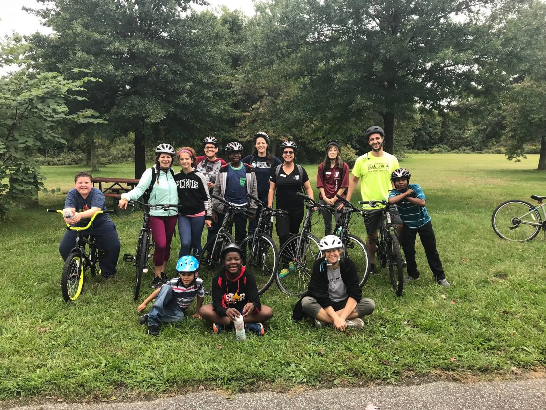 a group of multicultural teens and young adults pose with bikes & helmets in a natural setting.